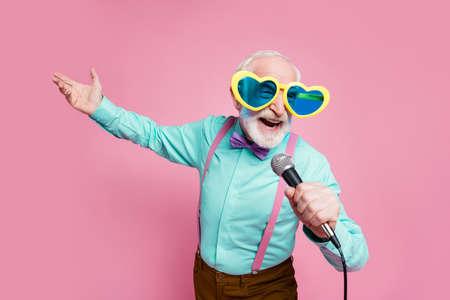 Foto de abuelo con estilo divertido emociones positivas sosteniendo micrófono de karaoke cantando canciones de fiesta usan especificaciones geniales camisa tirantes pajarita pantalones aislados fondo de color rosa pastel