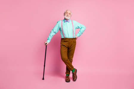 Full length photo of attractive grandpa good mood stand confident lean walking stick wear mint shirt suspenders bow tie brown pants boots green socks isolated pink pastel background
