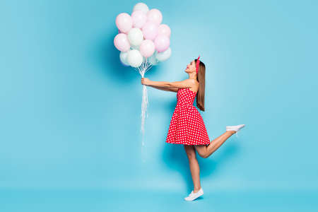 Full length body size profile side view of nice attractive girlish cheerful cheery straight-haired girl holding air balls having fun posing isolated on bright vivid shine vibrant blue color background