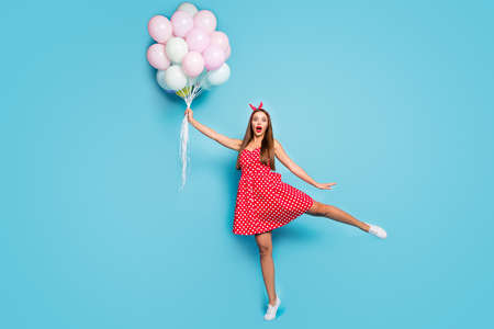 Full length body size view of nice attractive lovable girlish funny funky comic cheerful straight-haired girl holding air balls having fun isolated on bright vivid shine vibrant blue color background