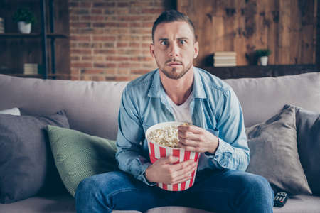 Photo of domestic handsome guy relaxing stay home quarantine time watch television horror movie eat popcorn terrified sit cozy sofa modern interior living room indoors