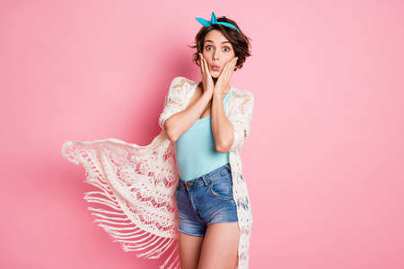 Photo of beautiful attractive lady excited facial expression arms on cheekbones party wear headband lace cloak singlet denim shorts isolated pastel pink color background