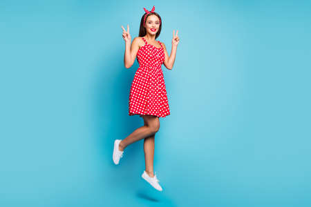 Full length body size view of her she nice-looking attractive optimistic cheerful cheery straight-haired girl jumping showing v-sign isolated on bright vivid shine vibrant blue color background