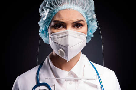 Closeup photo of serious infection disease doc experienced surgeon wear medical stethoscope lab coat mask facial plastic protection shield surgical cap hat isolated black background