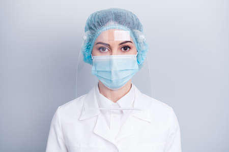 Closeup photo of attractive serious infection disease doctor after surgery operation tired eyes wear medical gown coat facial mask head plastic protect surgical cap isolated grey background