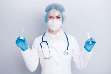 Photo of nurse lady doc hold test tube saliva collect equipment examining sick patient wear latex gloves mask coat facial plastic surgical cap isolated grey color background