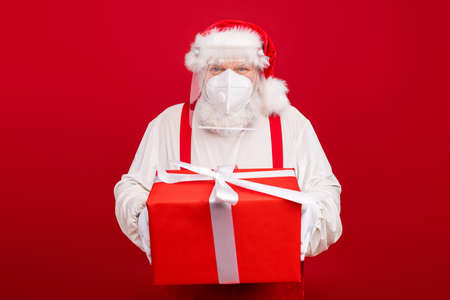 Photo of old bearded merry santa worker distance work take clients order big gift box delivery home holiday wear protect plastic shield face mask hat shirt suspenders isolated red background