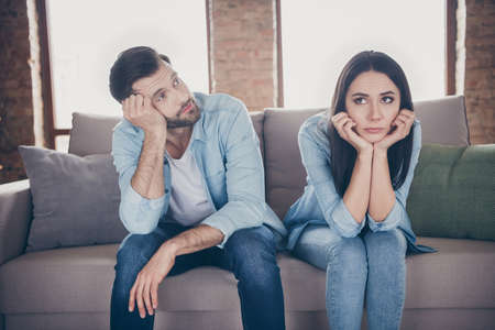 Portrait of stressed frustrated couple man woman sit divan have nothing to do on corona virus quarantine feel bored look touch hands face wear denim jeans shirt in house indoors