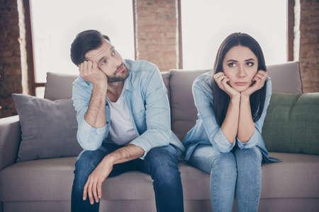 Portrait d'un couple frustré stressé homme femme assis sur le divan n'a rien à faire sur la quarantaine du virus corona se sentir ennuyé regarder toucher les mains le visage porter une chemise en jean dans la maison à l'intérieur