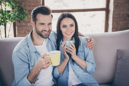 Portrait of affectionate caring two people spouses sit couch hug embrace man woman watch romantic series hold beverage mug in house indoors