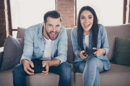 Portrait of his he her she nice attractive lovely excited glad cheerful friends friendship sitting on divan playing videogame having fun at modern brick loft industrial interior house flat