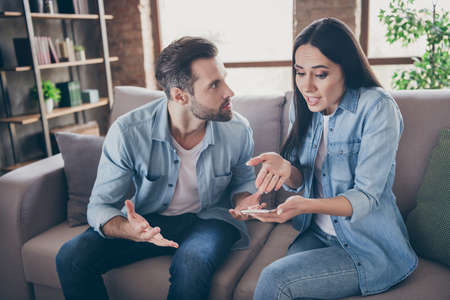 Photo of two people woman use smartphone try explain envy angry husband she dont have another man point hand screen feel confused sit comfort cozy couch in house indoors Standard-Bild