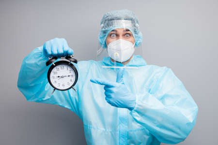 Photo of guy doc virology center eyes full fear hold alarm clock oversleep morning operation wear mask hazmat blue uniform suit plastic facial protect shield isolated grey color background