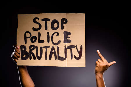 Close up photo of afro american hand hold banner stop police brutality show fuck symbol ignore haters fight rights isolated over black color background
