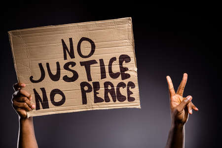 Close up photo of afro american person hand hold banner no peace no justice, make v-sign hope inspire symbol isolated over black color background