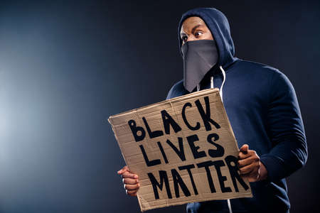 Profile side photo of shocked afro american guy hold banner impressed police community injustice racism issues wear sweater jumper isolated over black color background