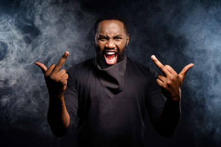 Photo of aggressive angry afro american guy show fucking symbol ignore racists shout scream wear jumper isolated over black smoke color background Фото со стока