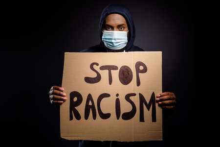 Photo of serious afro american guy hold card board banner stop racism share message human equality wear jumper medical mask isolated over black color background Stock fotó