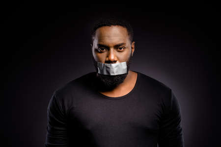 Portrait of frustrated voiceless speechless afro american guy have adhesive tape mouth cant speaking racism issue wear sweater isolated over black color background