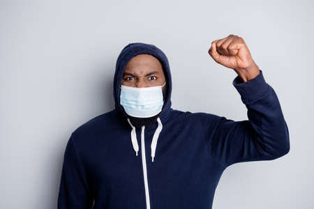 Photo of angry activist dark skin african protester demonstration police lawlessness politics lies raise fist strike scream through facial mask hood on head isolated grey color background