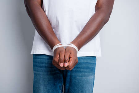 Cropped closeup photo of dark skin african guy tied with rope arms police took his freedom thief professional criminal dont have civil rights isolated grey color background 스톡 콘텐츠