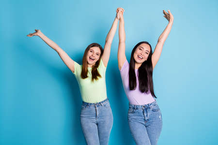 Photo of attractive crazy ladies lesbians couple raise hold arms overjoyed education college groupmates first year study wear casual t-shirts jeans isolated blue color background