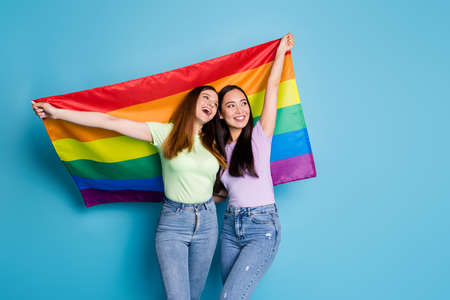 Photo of positive lesbians couple ladies walk foreign parade abroad country support all marriages raise flag look empty space wear casual t-shirts jeans isolated blue color background
