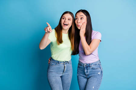 Photo of cheerful two people ladies lesbians couple hugging good mood communicating directing finger traveling sightseeing wear casual t-shirts jeans isolated blue color background