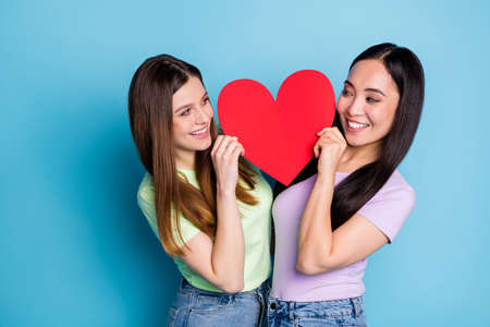 Photo of two funny lesbians couple ladies romance date hold big red paper heart shape lovers look eyes tricky flirty cunning wear casual t-shirts jeans isolated blue color background