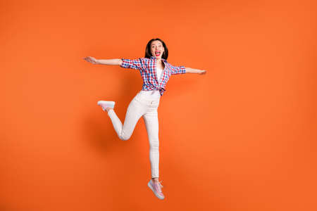 Yeah i can fly. Full size photo of crazy funky teenager girl jump hold hand imagine she pretty plane bird scream feel rejoice wear casual style clothing isolated orange color background Stok Fotoğraf