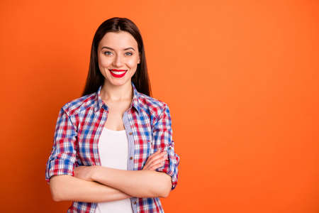 Portrait of her she nice-looking attractive content cheerful cheery straight-haired girl wearing checked shirt folded arms good mood isolated over bright vivid shine vibrant orange color background