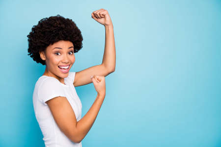 Goal. Profile photo of beautiful dark skin curly lady raising fists celebrating supporting football team match wear casual white t-shirt isolated blue color background