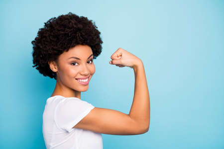 Closeup profile photo of beautiful dark skin curly lady showing perfect shape biceps after intense training gym wear casual white t-shirt isolated blue color background