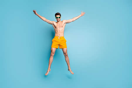 Full length body size view of his he nice attractive cheerful cheery funky guy in swimming shorts jumping up having fun isolated on bright vivid shine vibrant green blue turquoise color background