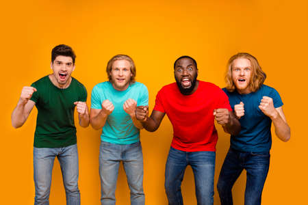 Photo of focused funky four men student watch national team league football match support hold fists ear t-shirt denim jeans isolated over bright color background
