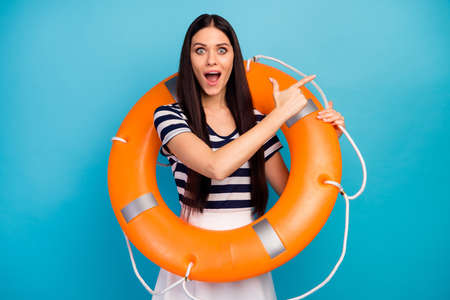 Photo of excited lady long hair hold orange emergency life buoy directing finger empty space advising cheap cruise liner trip wear white striped summer dress isolated blue background Foto de archivo