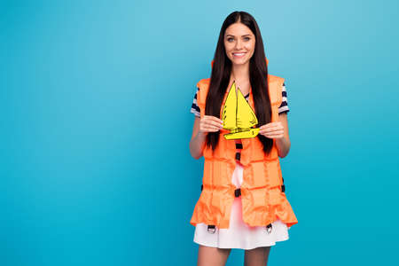 Photo of funny cheerful lady tourist long hairstyle orange emergency life vest hold painted yellow yacht wear white striped short summer dress isolated blue background Stok Fotoğraf