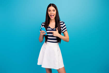 Photo of beautiful lady hold telephone directing finger smart phone screen shocked good wifi speed connection wear white striped short summer dress isolated blue background