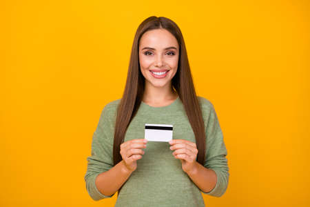 Portrait of style stylish positive cheerful girl hold credit card recommend online paying purchases saving salary earnings wear sweater isolated over bright color background