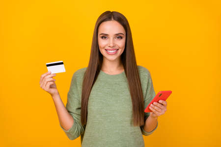Portrait of positive cheerful girl use cellphone show plastic card social media online banking user payer recommend buy online wear sweater isolated over bright shine color background Reklamní fotografie