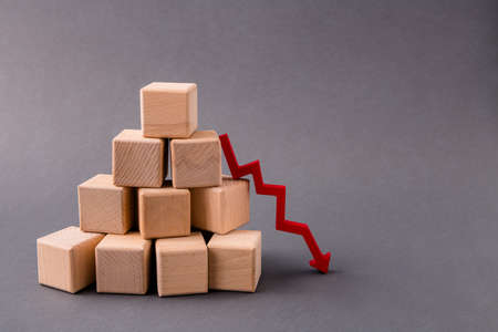 Photo of pile stack pyramid wooden cubes market supply sales falling down arrow pointing zero income money profit regress isolated over dark pastel grey color background