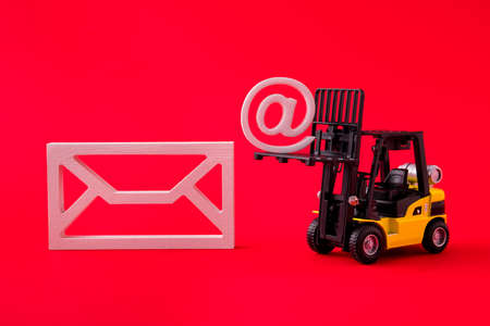 Close-up view of forklift carrying mailbox factory production partnership invite contact us supply management isolated over bright vivid shine vibrant red color background Stock Photo