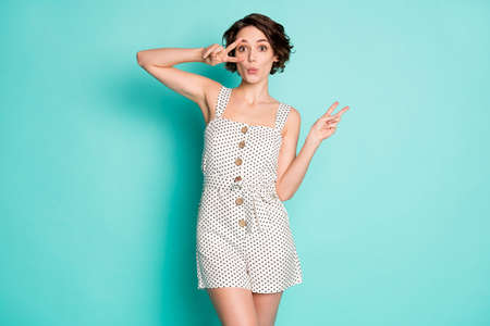 Photo of cheerful lady good mood showing v-sign symbols hands say hello friends send air kisses wear casual summer white dotted short overall isolated pastel teal color background