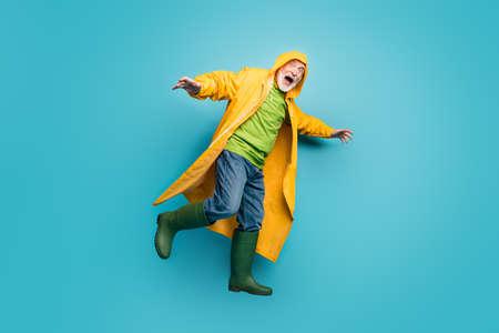 Full body profile photo of shocked grandpa amazed scream walk street puddles rainy weather wear jeans jumper rain boots yellow raincoat isolated blue color background