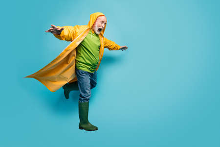 Full length photo of screaming grandpa amazed walk street puddles rainy weather slippery wet road wear jeans jumper gum boots yellow raincoat isolated blue color background