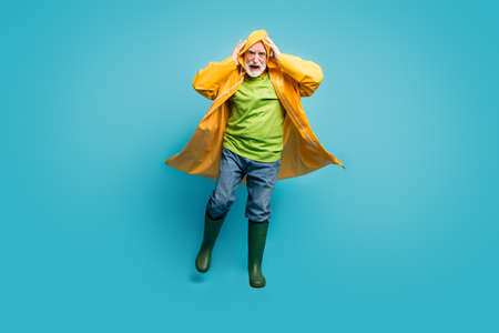 Full length photo of rushing home grandpa walk run street puddles, rainy weather slippery wet road wear jeans jumper gum boots yellow raincoat isolated blue color background