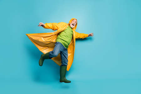 Full body photo of yelling grandpa amazed walk street puddles rainy, weather slippery wet road wear jeans jumper gum boots yellow raincoat isolated blue color background Stock Photo