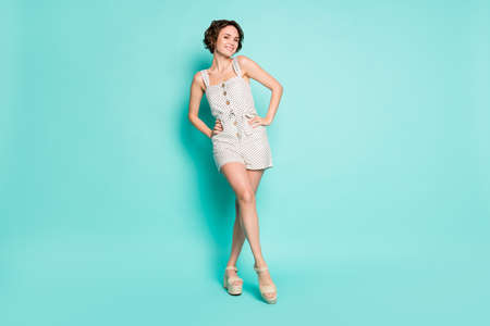 Full length photo of funny playful cheerful lady enjoy sunny day hold hands by sides wear casual summer white dotted overall shoes isolated pastel teal color background