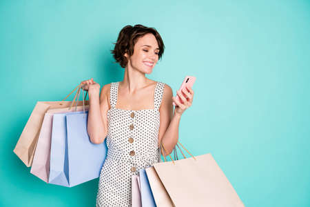 Portrait of her she nice attractive charming pretty glad cheerful cheery girl carrying brandy thing clothes using cell ordering web service isolated on bright vivid shine vibrant blue color background Standard-Bild