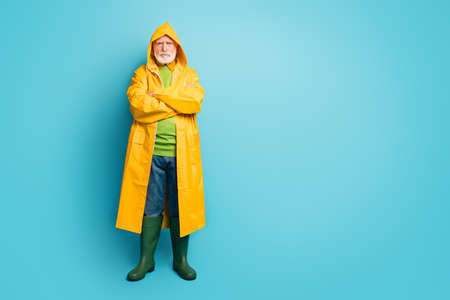 Full length body size view of his he nice serious sad grey-haired man fisherman, wearing long yellow topcoat folded arms bad weather isolated on bright vivid shine vibrant blue color background